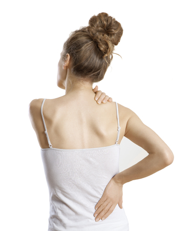 a young woman holds her back in pain, white background and isolated