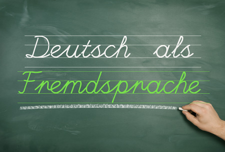 learners: a green school board with one hand and the text German Learners Dictionary Stock Photo