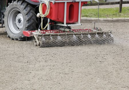suelo arenoso: un moderno planificador de picadero con riego por un tractor
