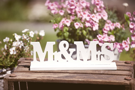 On a wooden background a sign Mr & Mrs and flowers as a background Banco de Imagens