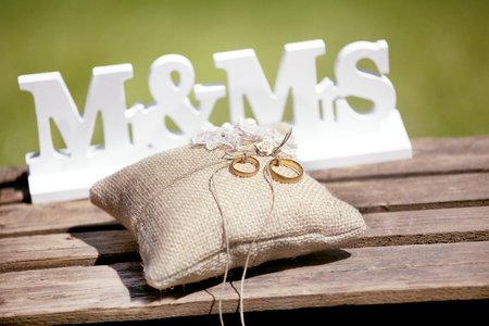 On a wooden floor a sign Mr & Mrs and a pillow with golden wedding rings