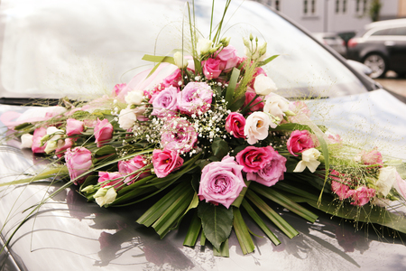 a beautiful bouquet of pink roses decorated on a wedding car