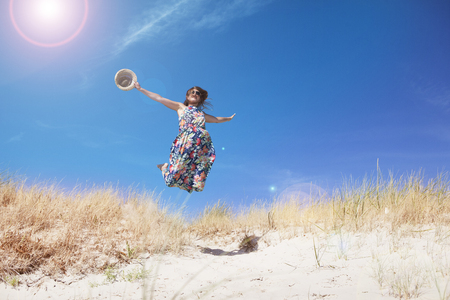 a young woman with long brown hair and sunglasses on the beach. jumps in the air