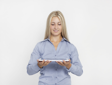 a young blond woman holds a tabletbook in her hands, isolated background