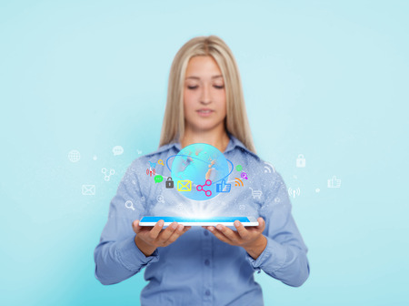 a young blond woman holds a tabletbook in her hands and surfs the internet