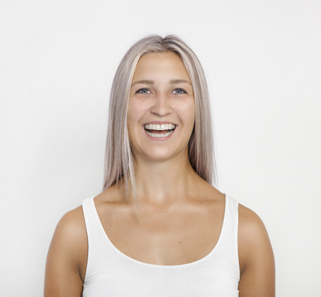 A young woman with modern silver hairstyle laughs at the camera, white background, isolated