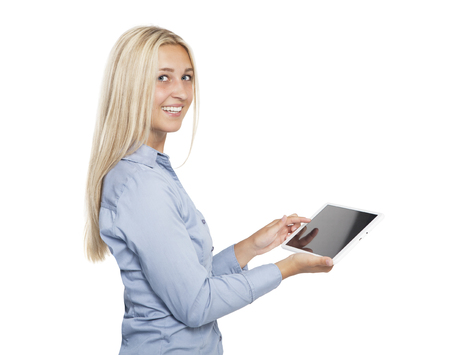 a young blonde woman with blue eyes holds a tabletbook in her hands and laughs at the camera, white background, isolated Reklamní fotografie
