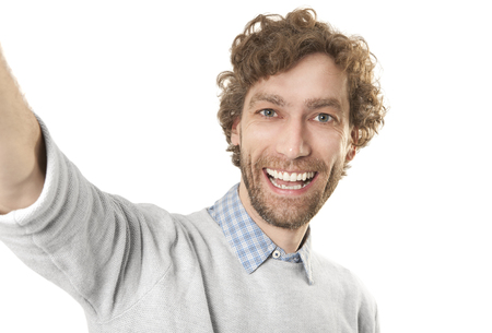a young laughing man makes a selfi against a white background