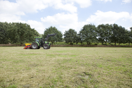 a modern tractor works the turf on a horse pasture Reklamní fotografie