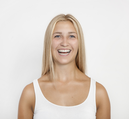 a young blond woman with blue eyes laughs at the camera, white background, isolated Reklamní fotografie