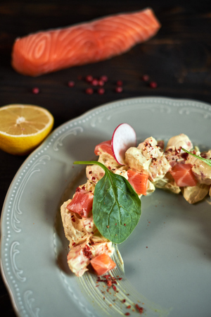 Salad with salmon and radish in the form of a month on a plate jpg