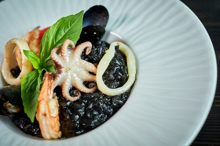 Dish of risotto with squid ink on grey plate
