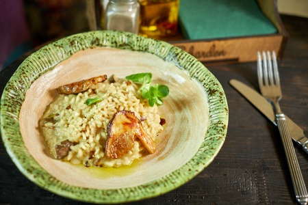 portobello: Risotto with chicken, peas and tomatoes on a wooden board, Italian food
