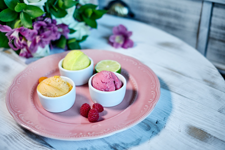 sorts: Selection of gourmet flavours of Italian ice cream in vibrant colors served in individual porcelain cups on an old rustic wooden table in an ice cream parlor, angle view jpg