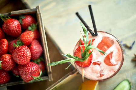 Strawberry lemonade with lime and ice in mason jar on a wooden table jpg
