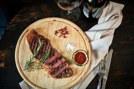 black angus cattle: Sliced medium rare grilled steak on rustic cutting board with rosemary and spices , dark rustic metal background, top view, place for text jpg Stock Photo
