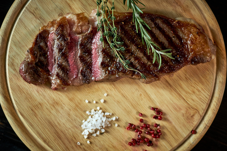 Sliced medium rare grilled steak on rustic cutting board with rosemary and spices , dark rustic metal background, top view, place for text jpg Stok Fotoğraf