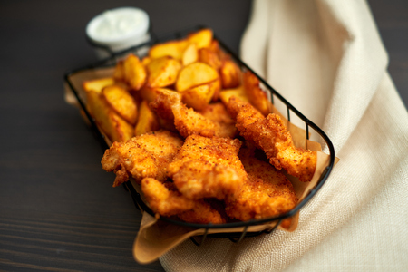 Nuggets and baked potatoes in a beautiful basket with white sauce