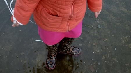 Little beautiful girl jumping on puddles after rain 4k Foto de archivo