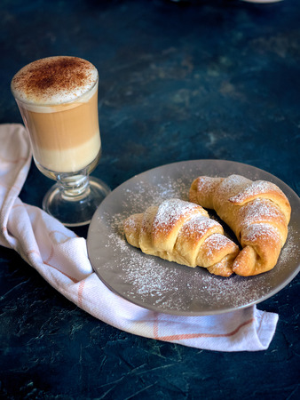 A cup of fresh coffee with croissants on a dark blue background, selective focus Standard-Bild - 109329106