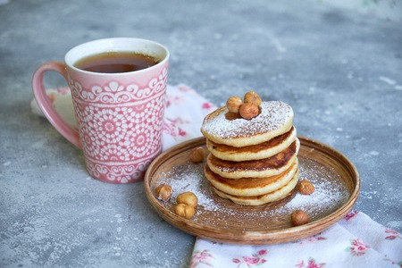 pancakes sprinkled with nuts hazelnuts on a plate with a napkin on a concrete background Standard-Bild - 109329116
