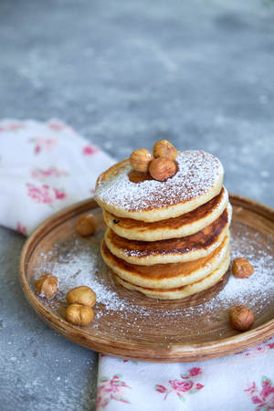 pancakes sprinkled with nuts hazelnuts on a plate with a napkin on a concrete background Standard-Bild - 109329818