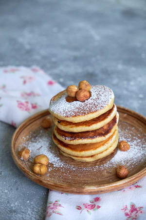 pancakes sprinkled with nuts hazelnuts on a plate with a napkin on a concrete background Standard-Bild - 109329819