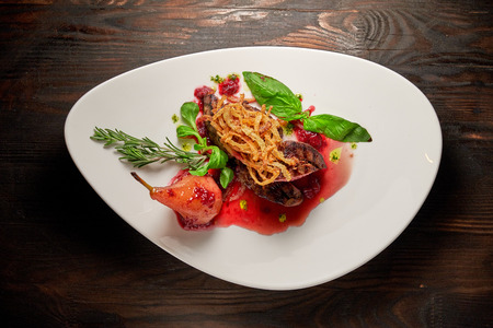 Meat steak with pear on a white plate. Dark wooden background. Restaurant food. Stock fotó