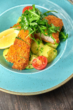 Breaded chicken with vegetables and herbs on a blue plate. Dark wooden background. Restaurant food. Imagens
