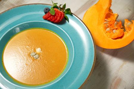 Puré de sopa de calabaza en un plato azul con semillas de calabaza. Fondo de madera clara.