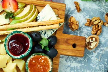 Cheese platter on a wooden board. Restaurant menu