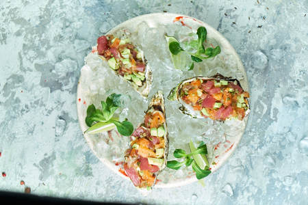 Tartar from fish in a cockleshell. Beautiful serving dishes. Light gray background. Restaurant menu