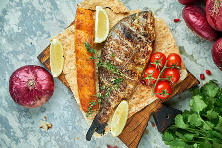Grilled dorado fish and salmon steak on a wooden board Stock Photo