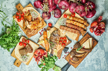 Plates of meat with barbecue and kebab, top view on gray background