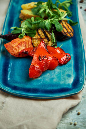 grilled vegetables and rustic potatoes on a  blue plate