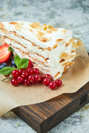Strawberry meringue cake with almond petals, on newspaper 写真素材