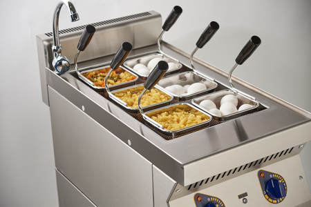 Steam electric stove for second courses. Mesh baskets are filled with pasta. Kitchen industrial equipment. common food