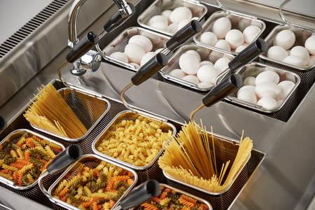 Dampf-Elektroherd für zweite Gänge. Gitterkörbe werden mit Nudeln gefüllt. Industrielle Küchengeräte. gewöhnliches Essen Standard-Bild