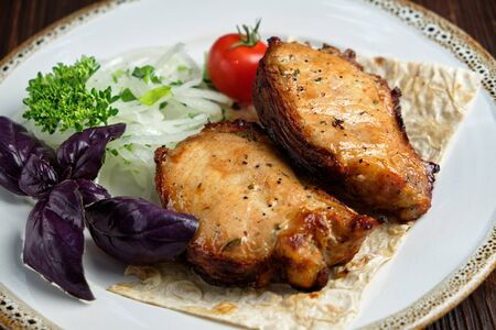 Skewers of chicken with thin pita bread on a white plate on a dark wooden background.