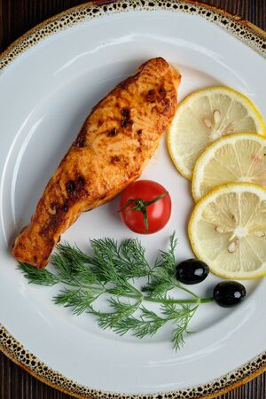 Grilled salmon steak with side dish on a white plate on a dark wooden background. Stockfoto - 130093868