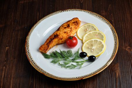 Grilled salmon steak with side dish on a white plate on a dark wooden background. Stockfoto - 130094237
