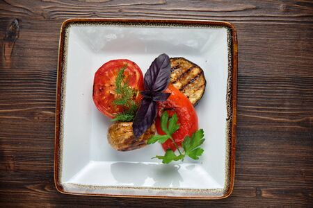 Grilled vegetables on a white plate on a dark wooden background. Stock Photo