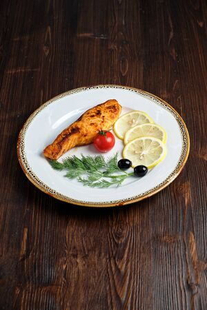 Grilled salmon steak with side dish on a white plate on a dark wooden background. Stockfoto - 130094696