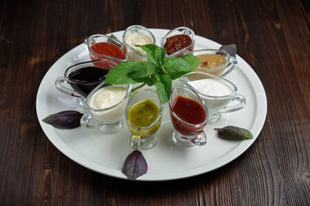 colored sauces in bowls on a white round plate on a dark wooden background. Stock fotó