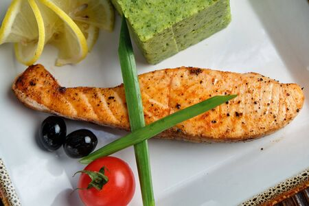 Grilled salmon steak with side dish on a white plate on a dark wooden background. Stockfoto - 130094699