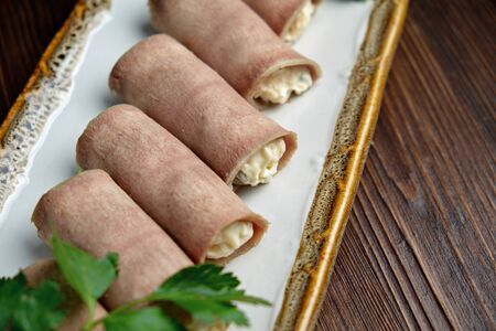 ham rolls with filling decorated with greens on a rectangular white plate on a dark wooden background.