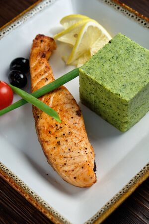 Grilled salmon steak with side dish on a white plate on a dark wooden background.