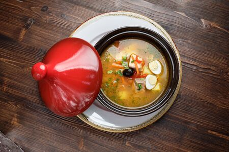 Fish soup in a pot with a red lid. catering menu