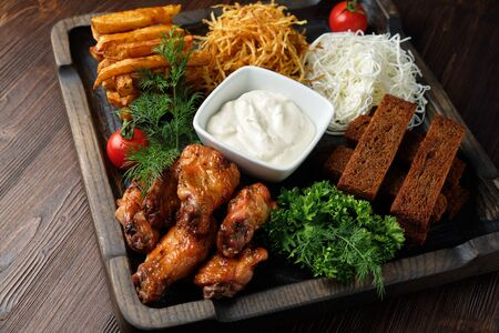 Hot appetizer on a wooden black plate on a dark wooden background. Restaurant menu Stock Photo