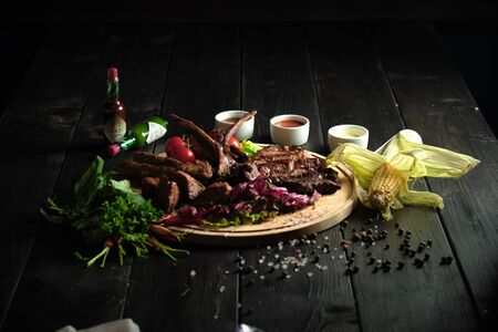 Meat on the bone on a wooden board . catering menu